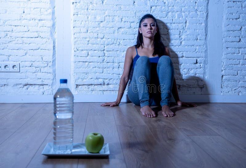 La giovane donna affamata depressa sulla mela e l'acqua sono a dieta fotografie stock