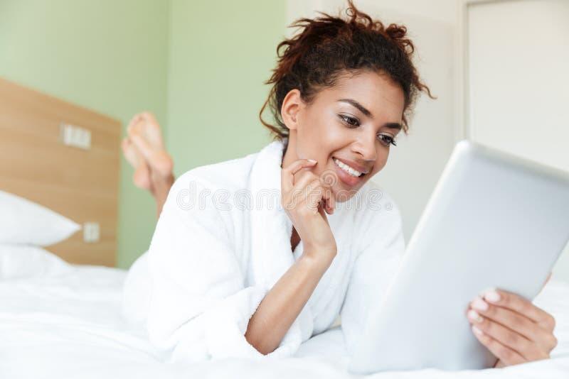 La giovane donna africana felice si trova sul letto all'interno immagini stock libere da diritti