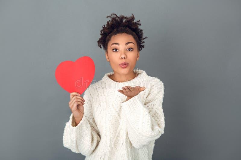 La giovane donna africana isolata sul concetto grigio dell'inverno dello studio della parete si bacia fotografie stock libere da diritti