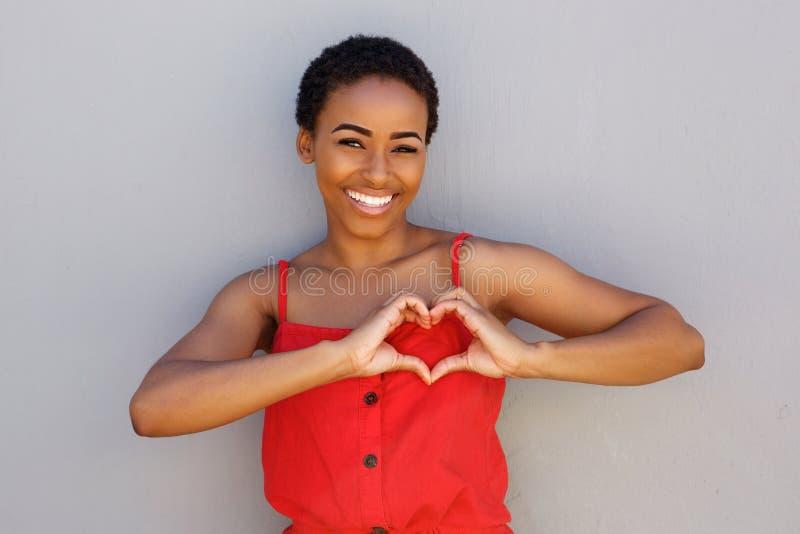 La giovane donna afroamericana sorridente con cuore modella il segno della mano immagine stock