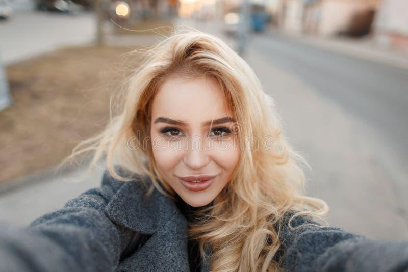 La giovane donna alla moda in cappotto grigio fa il selfie fotografia stock libera da diritti