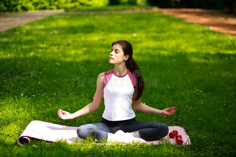 La giovane donna allegra che si rilassa in sole, facente l'yoga si esercita immagini stock