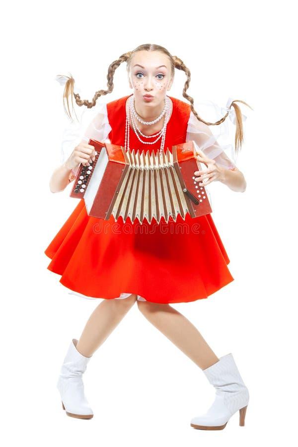 La giovane donna allegra graziosa con le intrecciature ridicole in costume piega russo gioca una fisarmonica immagini stock