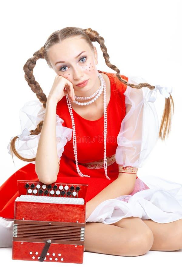 La giovane donna allegra graziosa con le intrecciature ridicole in costume piega russo gioca una fisarmonica fotografia stock
