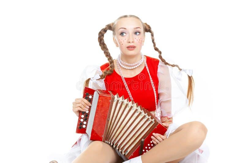 La giovane donna allegra graziosa con le intrecciature ridicole in costume piega russo gioca una fisarmonica immagini stock libere da diritti