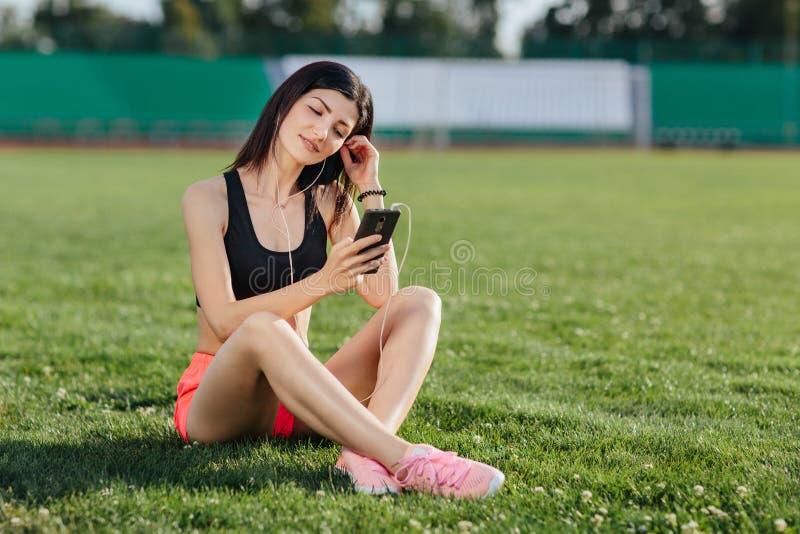 La giovane donna allegra sportiva castana in breve e la cima che si siedono sullo stadio del campo di football americano dell'erb fotografie stock