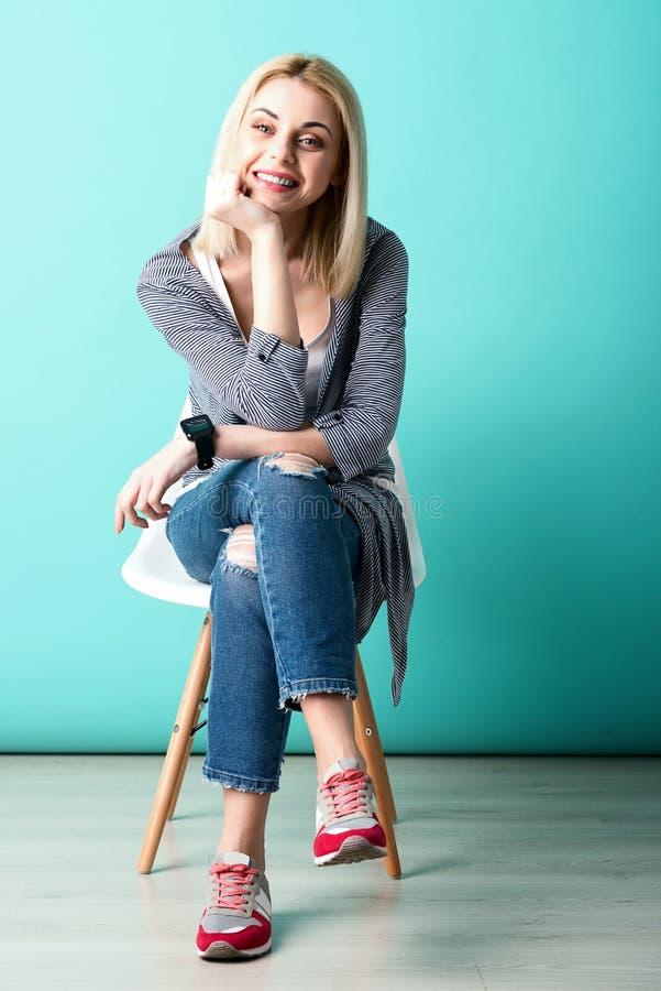 La giovane donna allegra sta sedendosi con l'anticipazione immagine stock