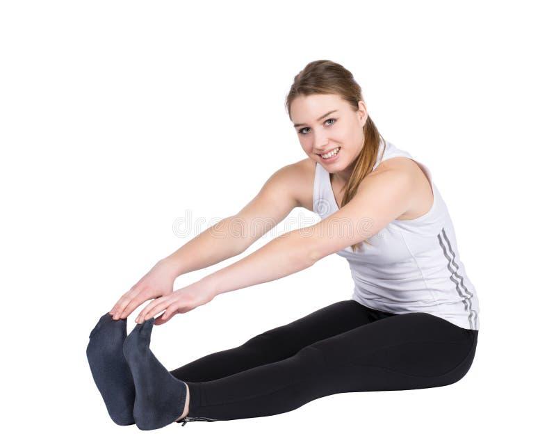 La giovane donna allunga la sua muscolatura fotografia stock libera da diritti