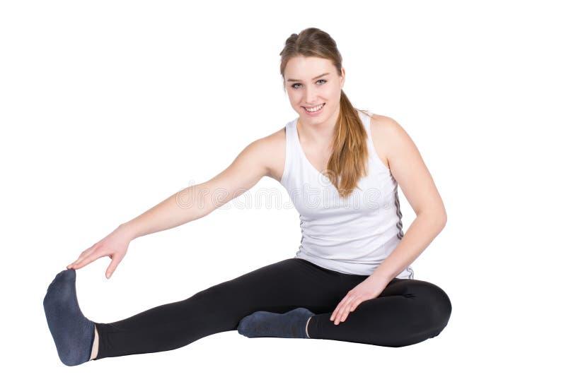 La giovane donna allunga la sua muscolatura fotografia stock