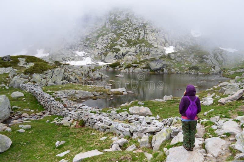La giovane donna ammira un lago della montagna in nebbia fotografia stock