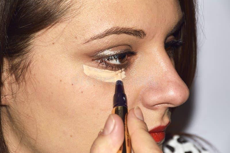 La giovane donna applica il correttore sotto l'occhio fotografie stock