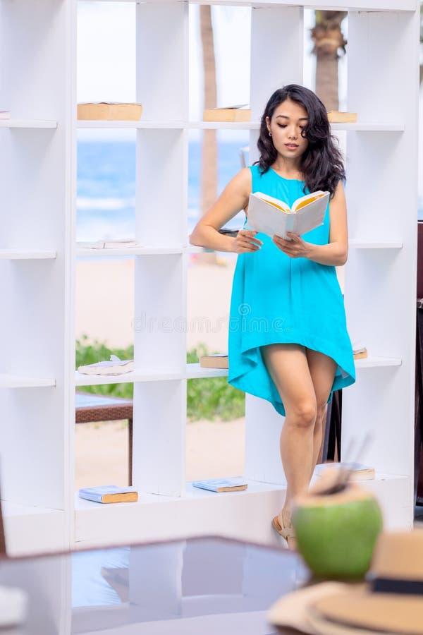 La giovane donna asiatica è libro di lettura alla biblioteca all'aperto della spiaggia immagini stock
