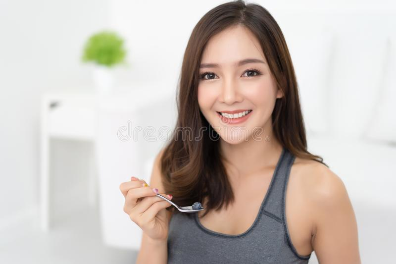 La giovane donna asiatica ? riposante e mangiante un yogurt greco con il blu fotografia stock