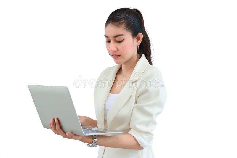 La giovane donna asiatica attraente di affari con il computer portatile su bianco ha isolato il fondo fotografia stock