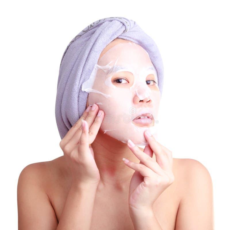 La giovane donna asiatica che applica il facial pela la maschera fotografia stock