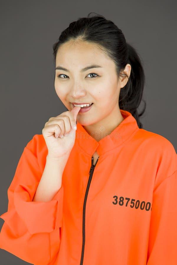 La giovane donna asiatica che sorride nei prigionieri uniforma con il dito in bocca fotografia stock