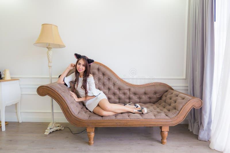 La giovane donna asiatica del gatto sta trovandosi su uno strato nella stanza moderna immagini stock