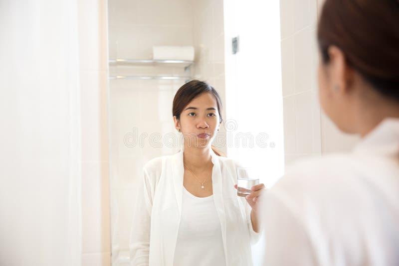 La giovane donna asiatica fa i gargarismi sulla sua bocca dopo la spazzolatura di dente immagine stock