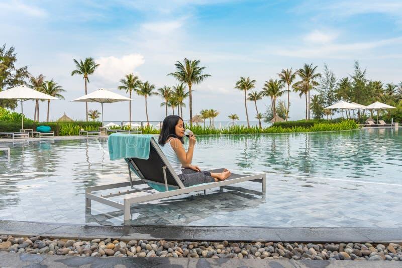 La giovane donna asiatica gode del vino rosso alla bella piscina fotografia stock libera da diritti