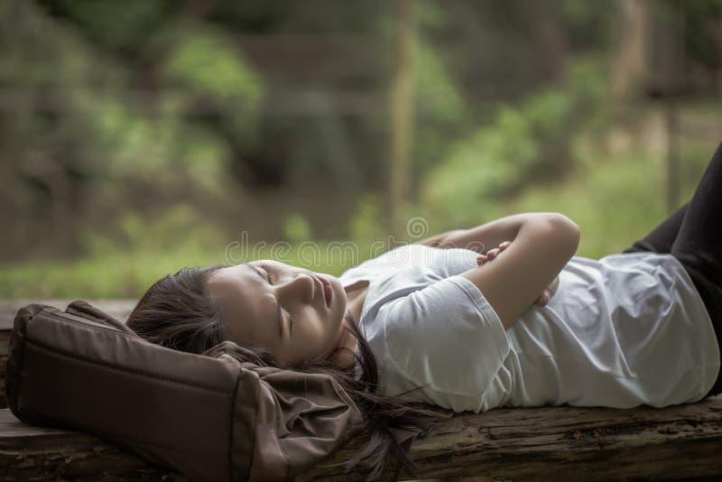 La giovane donna asiatica indica sullo zaino e sul sonno sul benc di legno immagine stock