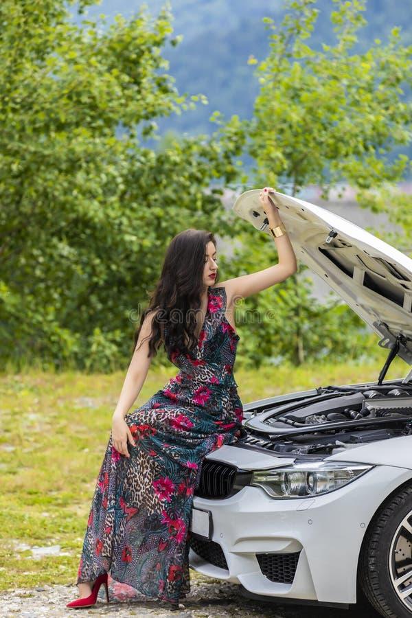 La giovane donna aspetta l'assistenza vicino alla sua automobile ripartita sul immagine stock