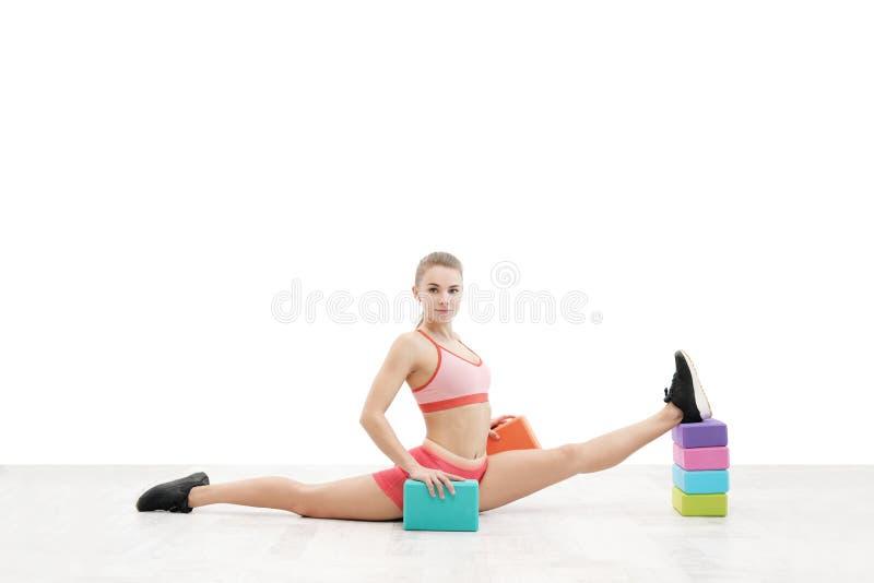 La giovane donna atletica con un corpo atletico, le cuffie senza fili d'uso e gli abiti sportivi rossi è allungata sui blocchetti fotografia stock