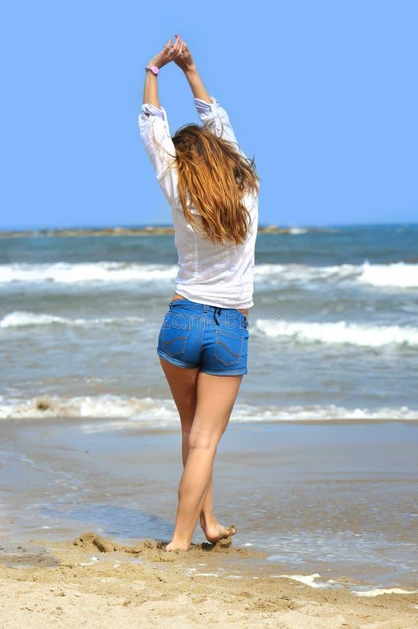 La giovane donna attraente in breve dentro si rilassa alla spiaggia nella libertà co fotografia stock