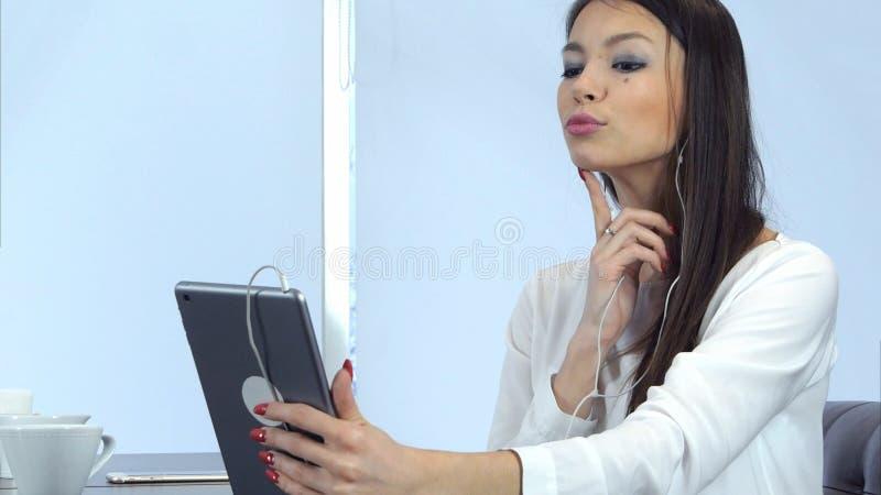 La giovane donna attraente che la controlla compone per mezzo della compressa e preparando per la video chiamata immagini stock libere da diritti