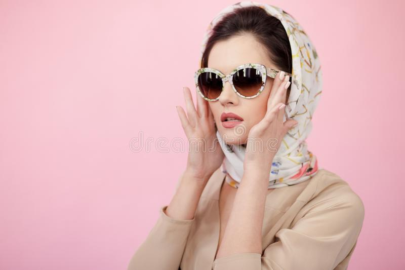 La giovane donna attraente che dura in sciarpa di seta, tocca i suoi occhiali da sole con le sue mani, isolate su fondo rosa fotografia stock libera da diritti
