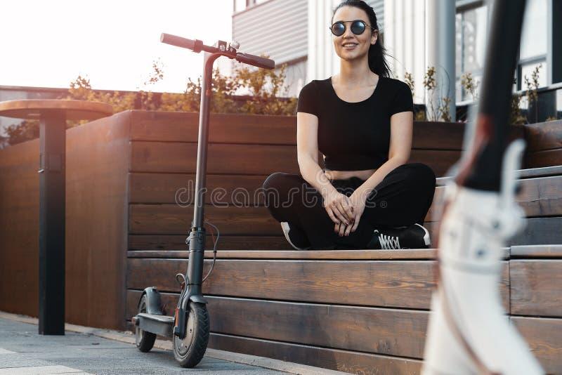 La giovane donna attraente che si siede accanto al electrick dà dei calci al motorino il parco moderno immagini stock