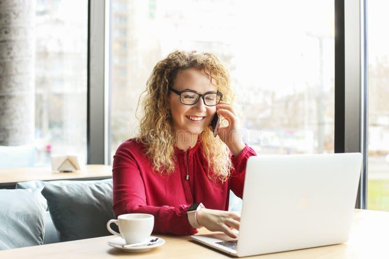 La giovane donna attraente che si siede alla caffetteria con il suo computer portatile alla moda, cappuccino bevente, parlando su fotografia stock