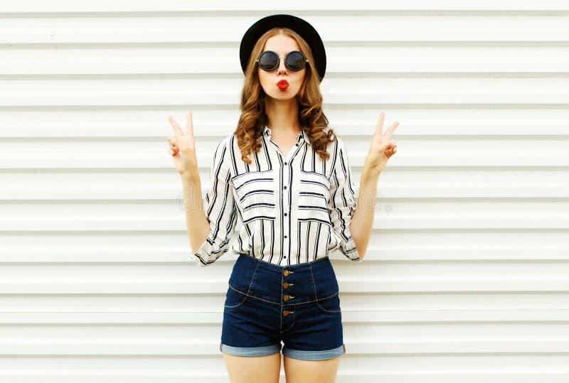 La giovane donna attraente che soffia le labbra rosse che inviano il bacio dolce dell'aria in cappello rotondo nero, mette, camic immagini stock libere da diritti