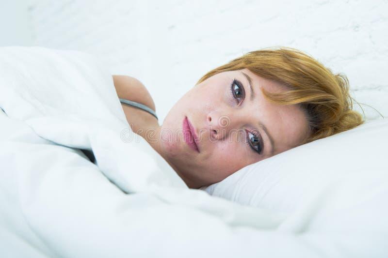 La giovane donna attraente con i grandi bei occhi apre la menzogne a letto nell'espressione misteriosa del fronte fotografia stock libera da diritti