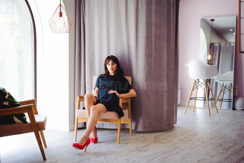 La giovane donna attraente con le gambe lunghe in vestito elegante nero, si siede in sedia vicino alla finestra nell'interno di s immagini stock libere da diritti