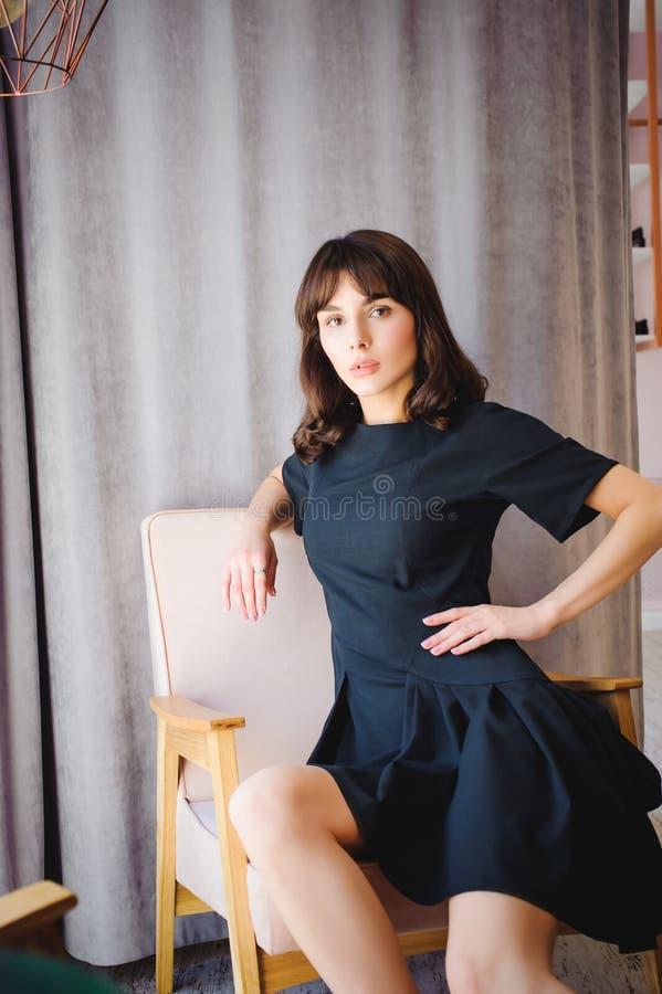 La giovane donna attraente con le gambe lunghe in vestito elegante nero, si siede in sedia vicino alla finestra nell'interno di s immagine stock libera da diritti