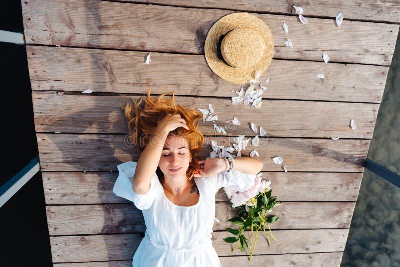 La giovane donna attraente dei pantaloni a vita bassa in vestito bianco si trova sul pavimento di legno immagini stock libere da diritti