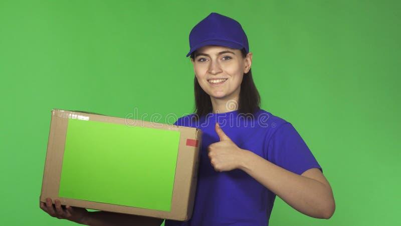 La giovane donna attraente della consegna che mostra i pollici aumenta la scatola di cartone della tenuta fotografie stock