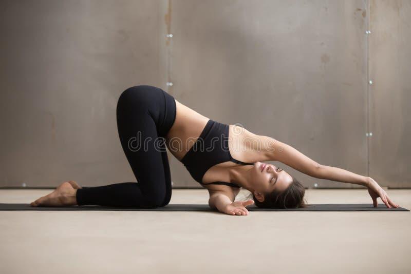 La giovane donna attraente dentro infila la posa dell'ago, studio grigio fotografia stock