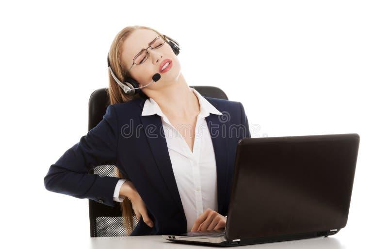 La giovane donna attraente di affari alla call center sta avendo backach immagine stock