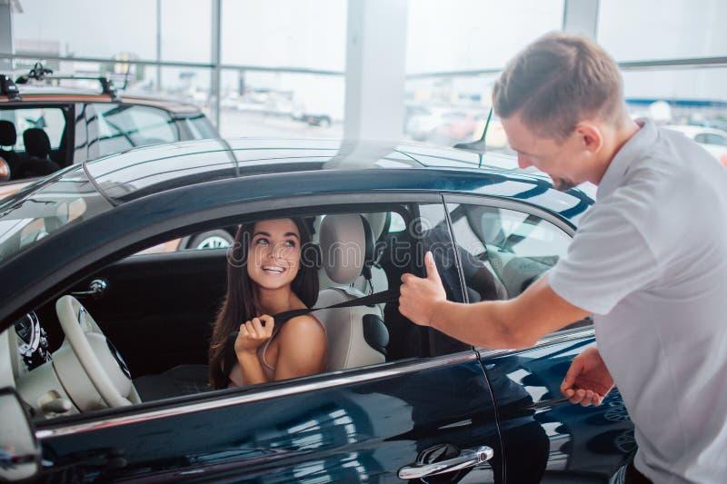 La giovane donna attraente e allegra si siede in automobile Esamina il consulente ed il sorriso a lui L'uomo tiene la porta con u fotografia stock