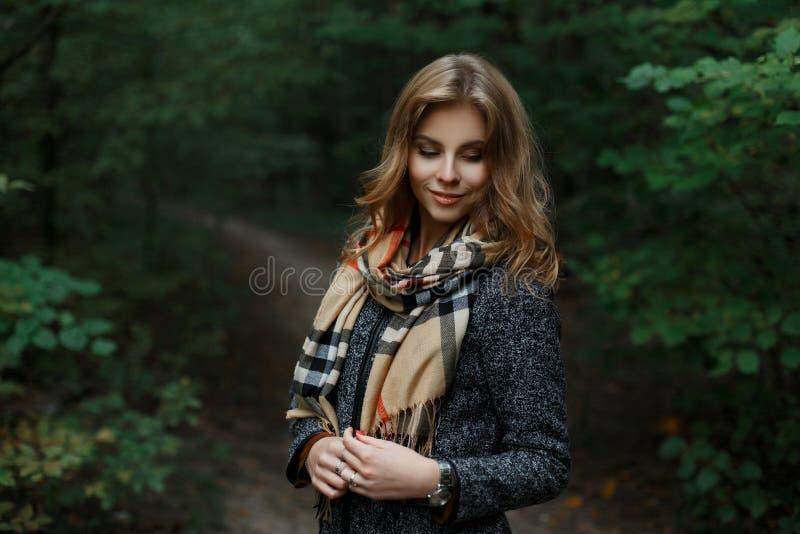 La giovane donna attraente felice in un cappotto grigio alla moda con una sciarpa a quadretti alla moda sta stando su un percorso immagini stock