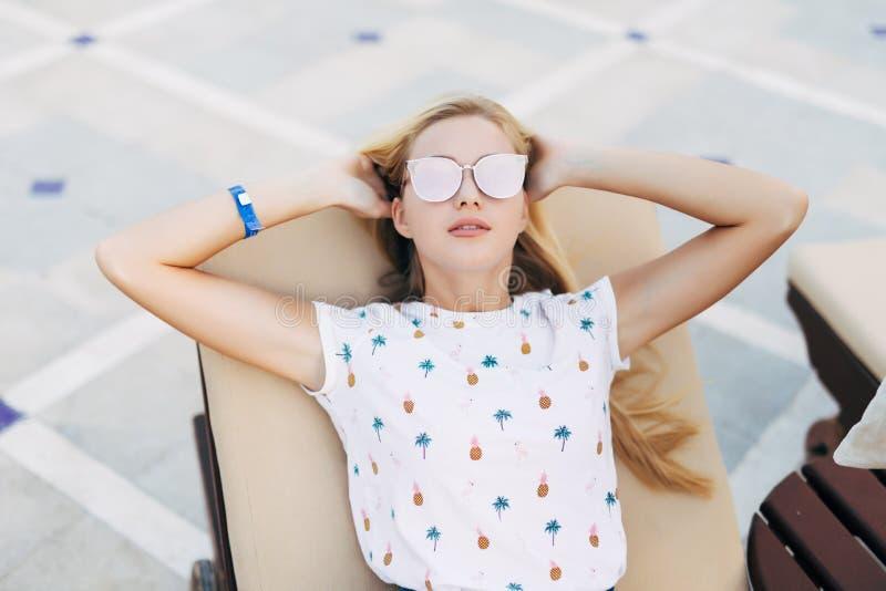 La giovane donna attraente in occhiali da sole sta trovandosi sulle chaise longue vicino alla piscina su ora legale fotografia stock libera da diritti