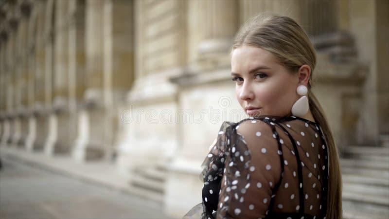 La giovane donna attraente sembra incantante sul fondo di vecchia costruzione azione Spalla esaminante sexy bionda alla macchina  fotografia stock