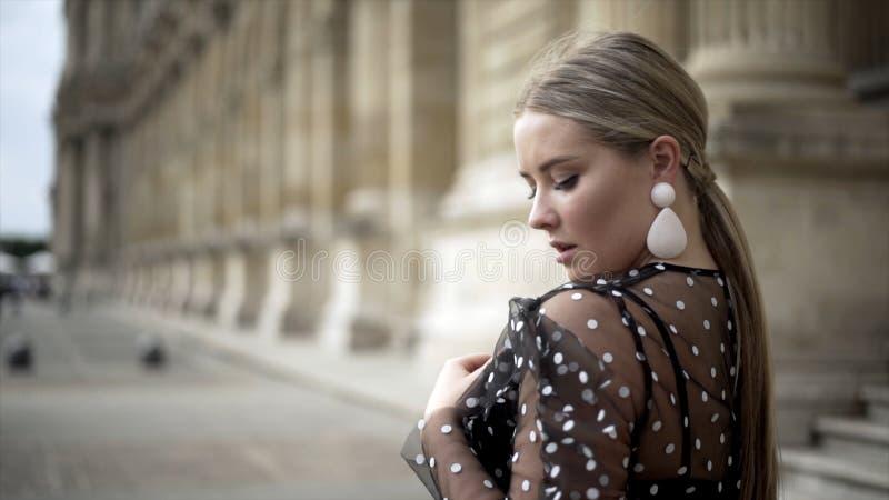 La giovane donna attraente sembra incantante sul fondo di vecchia costruzione azione Spalla esaminante sexy bionda alla macchina  fotografie stock libere da diritti