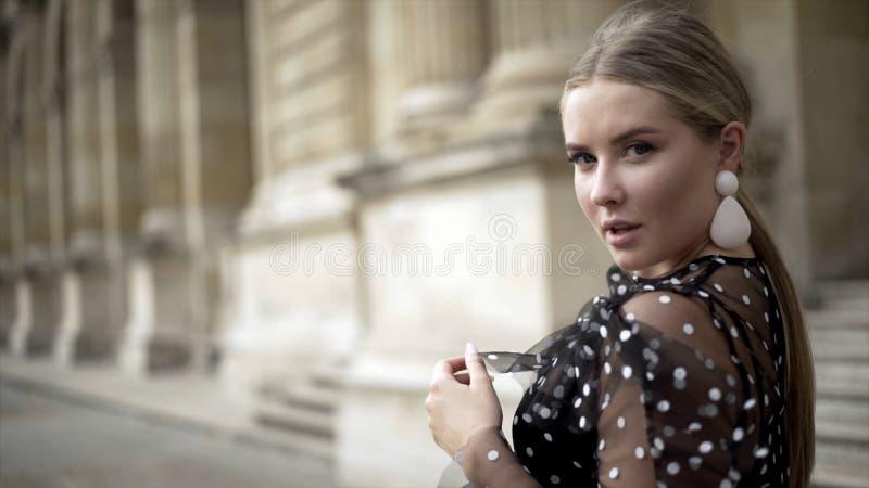 La giovane donna attraente sembra incantante sul fondo di vecchia costruzione azione Spalla esaminante sexy bionda alla macchina  fotografie stock
