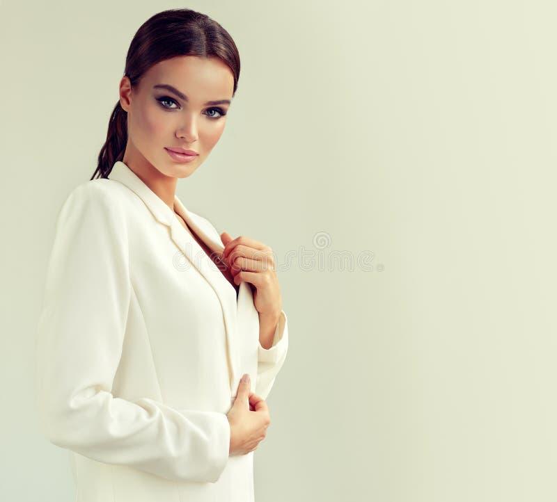 La giovane donna attraente si è vestita in un rivestimento bianco del vestito Trucco e cosmetologia fotografie stock