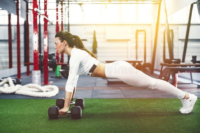 La giovane donna attraente sta facendo l'esercizio della plancia mentre risolveva nella palestra immagini stock