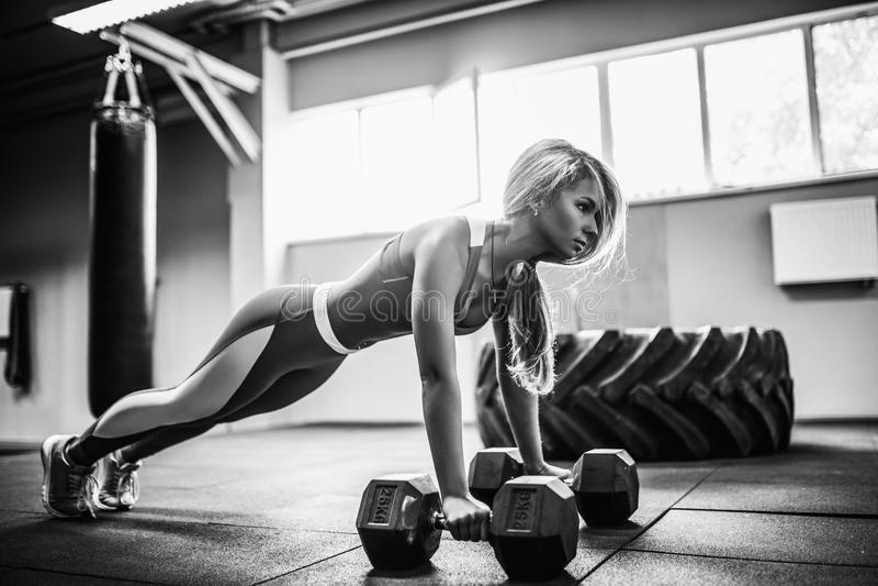 La giovane donna attraente sta facendo l'esercizio della plancia mentre risolveva nella palestra immagini stock libere da diritti
