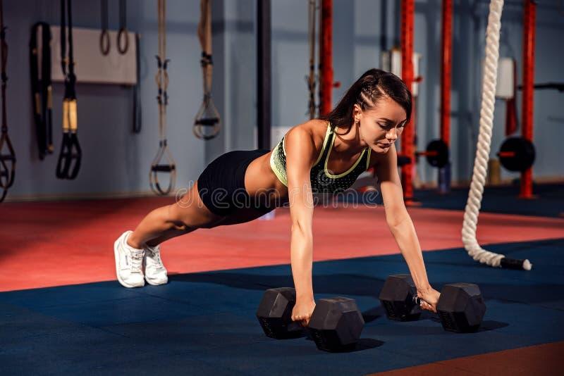 La giovane donna attraente sta facendo l'esercizio della plancia mentre risolveva nella palestra fotografia stock