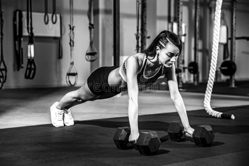 La giovane donna attraente sta facendo l'esercizio della plancia mentre risolveva nella palestra immagine stock libera da diritti